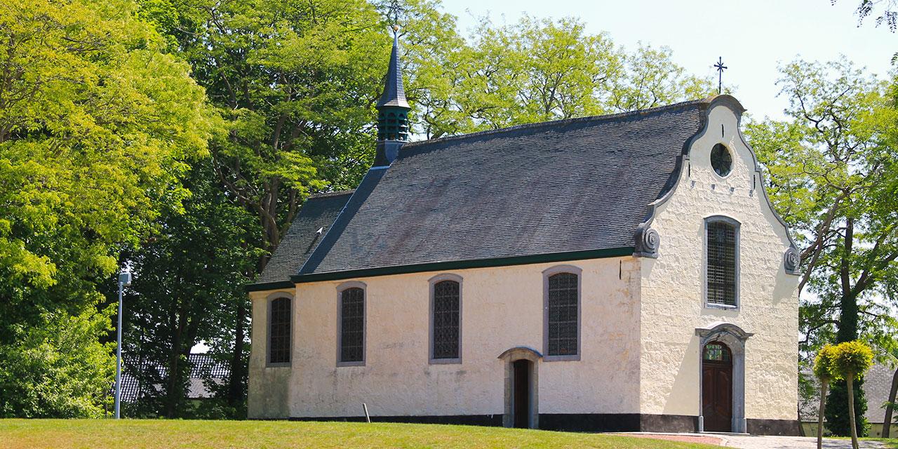 De Bareldonkkapel met witte muren, hoge ramen, zwart dak en een klein torentje staat te pronken tussen het groen.
