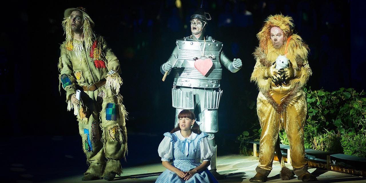 De vogelverschrikker, tinnen man en leeuw van De tovenaar van OS staan achter een zittende Dorothy.