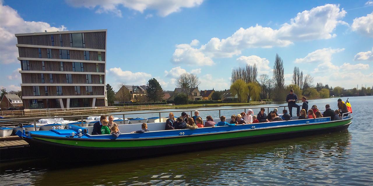 De blauw-groene overzetboot is bijna volzet en ligt aan de zonovergoten kade te wachten  op de laatste passagiers, klaar om te vertrekken.