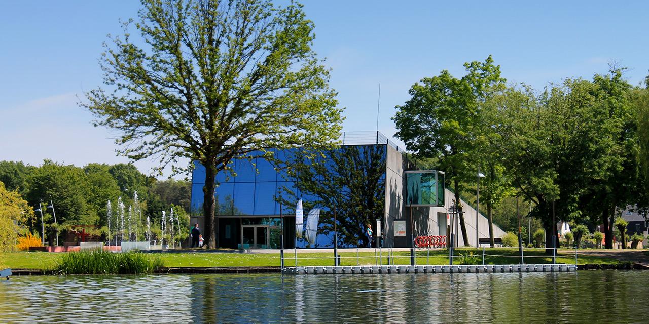 Het strak moderne gebouw van het toeristisch infokantoor reist uit het groen van de waterkant. Voor de ingang een machtige boom en enkele verfrissende fonteinen.