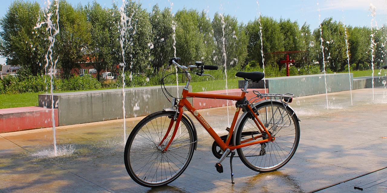 Een oranje fiets staat statig geparkeerd op de natte betonnen afwatering van de reeks fonteinen op de achtergrond.