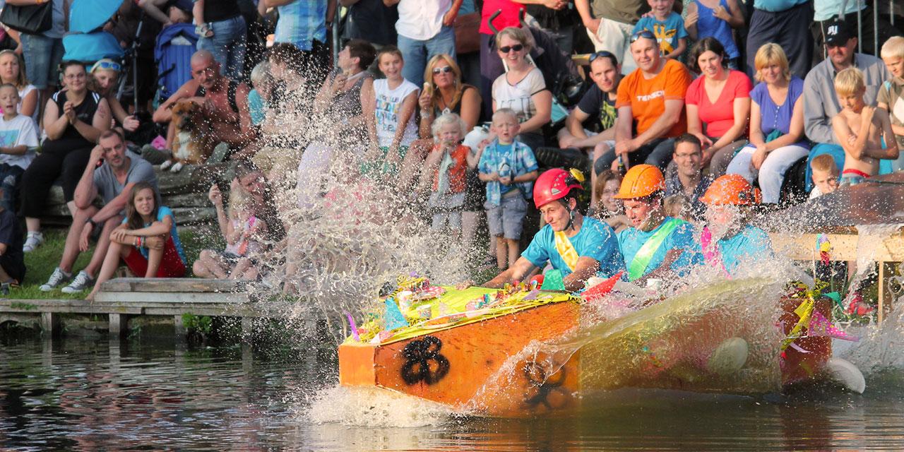Een oranje zelf geknutseld bootje, met drie jonge mannen aan boord, komt met een grote splash in het water nadat het net van een schans af gleed.